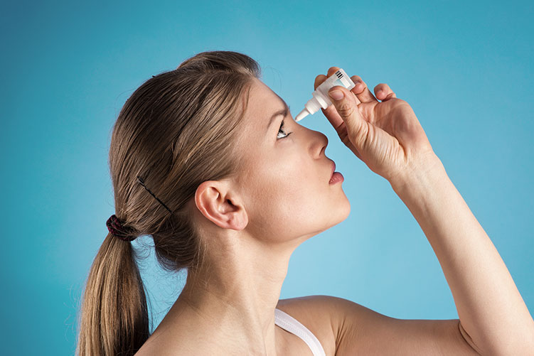 woman putting in eyedrops